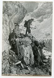 Wehrmacht Heer Pressefoto: Fest angedrückt an den Felsen sind die Männer geschützt vor Beschuss und Steinschlag